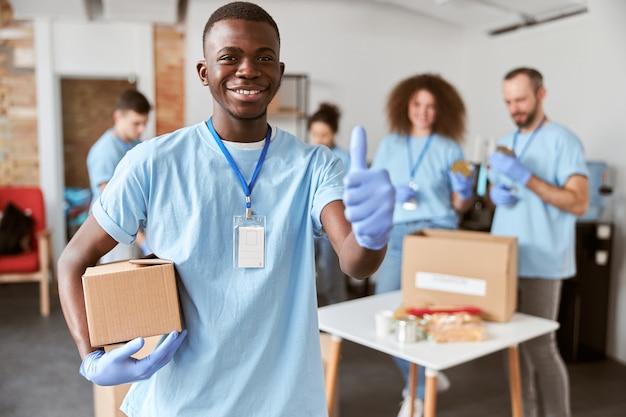 Portret van een afro-amerikaanse jonge mannelijke vrijwilliger in blauwe uniforme beschermende handschoenen die glimlacht naar