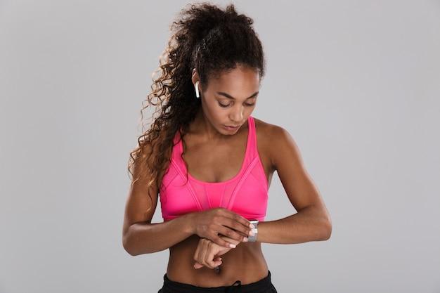 Portret van een afro-amerikaanse jonge sportvrouw geïsoleerd over grijze achtergrond, luisteren naar muziek met koptelefoon, kijken naar haar slimme horloge