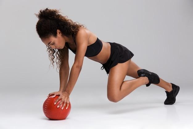 Portret van een afro-amerikaanse jonge sterke sportvrouw die oefeningen met zware bal doet die over grijze achtergrond worden geïsoleerd