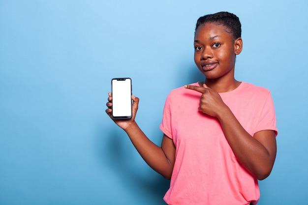 Portret van een afro-amerikaanse jonge vrouw die een telefoon vasthoudt met een wit leeg scherm
