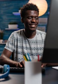 Portret van een afro-amerikaanse jonge werknemer die op afstand van huis werkt
