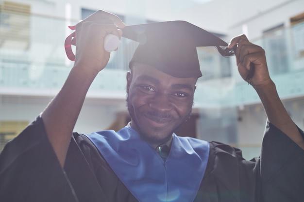 Portret van een afro-amerikaanse jongeman met een afstudeerhoed en glimlachend in de camera in zonlicht