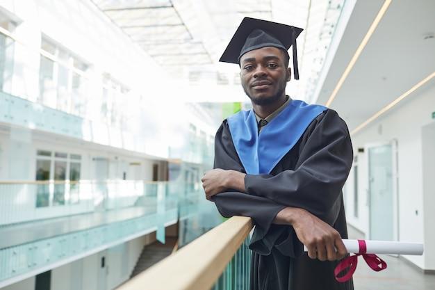 Portret van een afro-amerikaanse jongeman met een afstudeerjurk en een hoed die naar de camera kijkt terwijl hij binnenshuis poseert