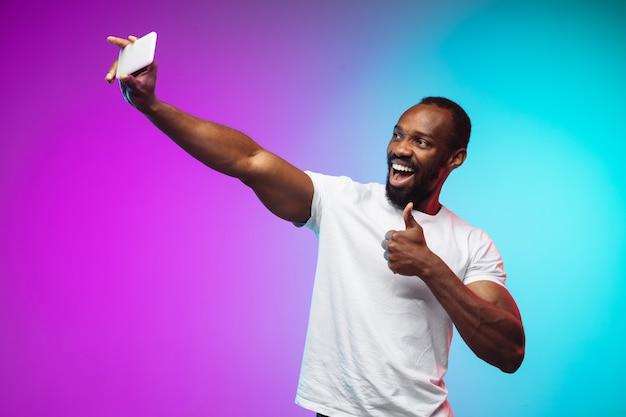 Portret van een afro-amerikaanse jongeman op gradiëntstudio in neon