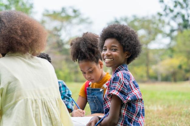 Portret van een afro-amerikaanse jongen of afro-jongen die met zijn vrienden op het gras zit en plezier heeft met potloden die op boeken tekenen in buiten klaslokalen in het park van de school. onderwijs buiten concept