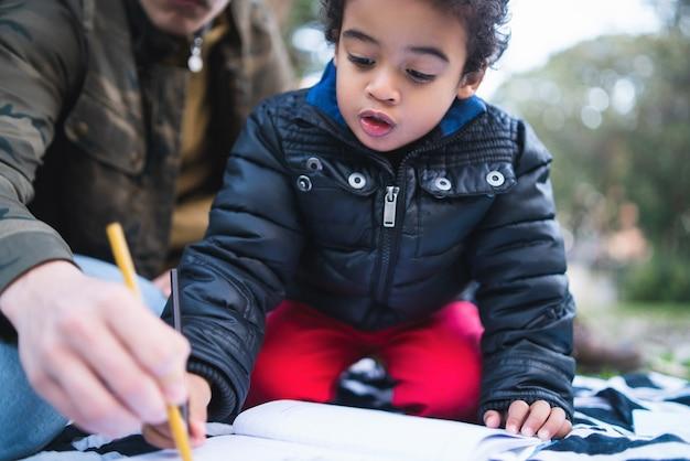 Portret van een afro-amerikaanse kleine jongen spelen en plezier maken met zijn vader buiten in het park. monoparentale familie.