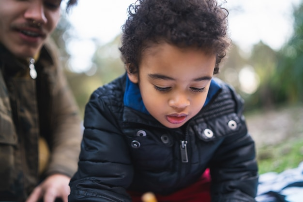 Portret van een afro-amerikaanse kleine jongen spelen en plezier maken met zijn vader buiten in het park