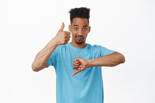 Portret van een afro-amerikaanse man die duimen op en neer laat zien, iets beoordeelt, gemiddeld middelmatig ding beoordeelt, fronsend verbijsterd om te antwoorden, staande op wit