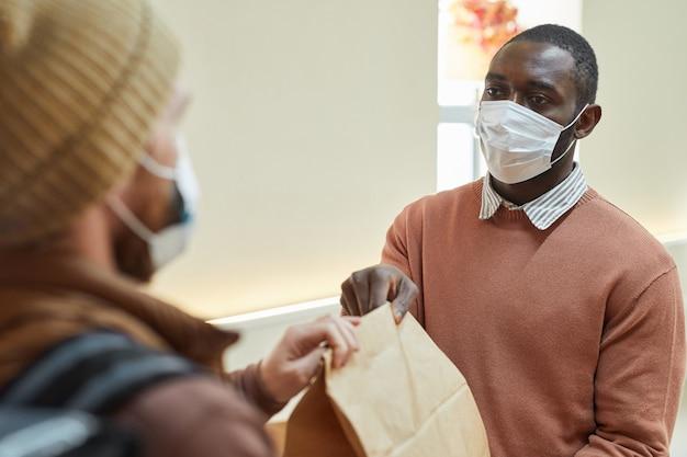 Portret van een afro-amerikaanse man die een afhaalbestelling overhandigt aan de klant in het café, beide met maskers, covid-beperkingenconcept