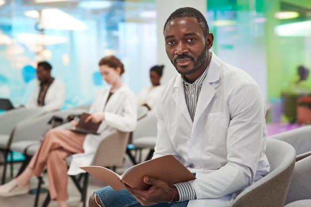 Portret van een afro-amerikaanse man die een laboratoriumjas draagt en naar de camera kijkt terwijl hij in het publiek zit en luistert naar een lezing over medicijnen, kopieer ruimte