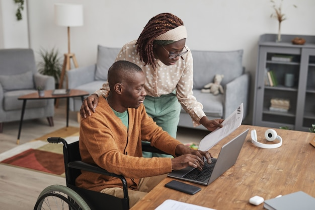 Portret van een afro-amerikaanse man die een rolstoel gebruikt die vanuit huis werkt met zijn vrouw die over zijn schouder kijkt, kopieer ruimte