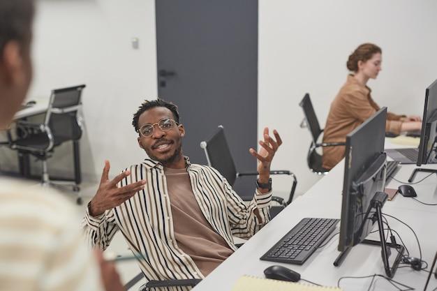 Portret van een afro-amerikaanse man die met een collega op kantoor praat en actief gebaart terwijl hij op de werkplek zit met een computer, kopieer ruimte