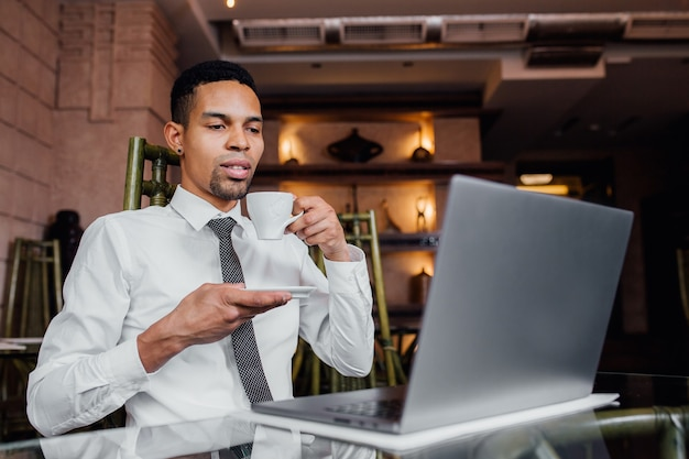 Portret van een afro-amerikaanse man drinkt koffie en werkt op een laptop, in een wit overhemd, binnen