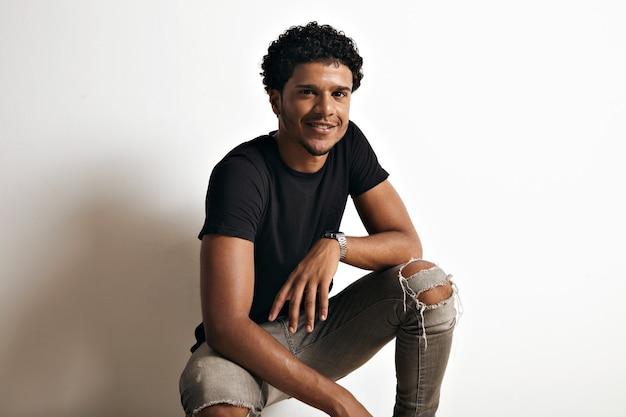 Portret van een afro-amerikaanse man in een zwart katoenen t-shirt en gescheurde spijkerbroek zittend aan de muur van een wit