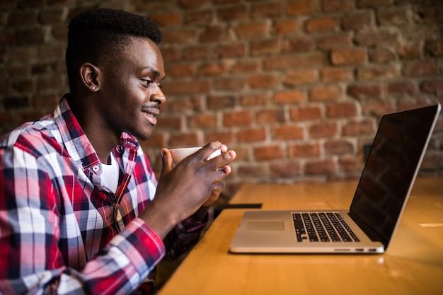 Portret van een afro-amerikaanse man koffie drinken en werken op een laptop in café
