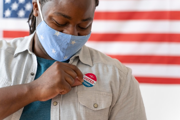 Portret van een afro-amerikaanse man met medisch masker op de dag van de kiezersregistratie