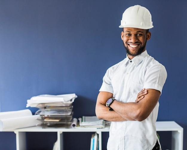 Portret van een afro amerikaanse mannelijke ingenieur die witte bouwvakker draagt