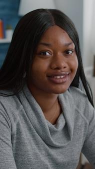 Portret van een afro-amerikaanse student die aan een bureautafel in de woonkamer zit en naar de camera kijkt