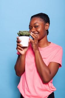 Portret van een afro-amerikaanse student die geniet van een tuinhobby met een bloempot