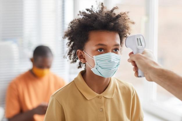 Portret van een afro-amerikaanse tienerjongen met een masker die temperatuurcontrole krijgt tijdens het wachten in de rij bij de kliniek, kopieer ruimte