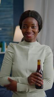 Portret van een afro-amerikaanse vrouw die in de camera glimlacht terwijl ze 's avonds laat een bierflesje in handen houdt...