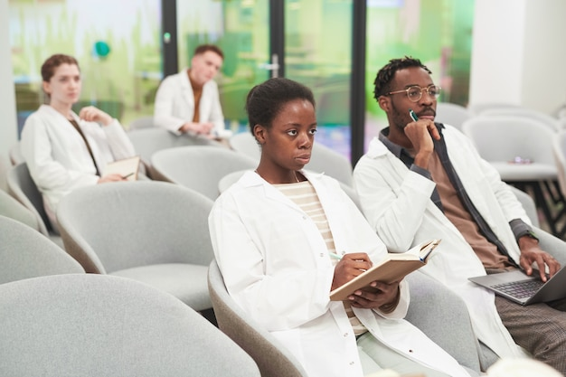 Portret van een afro-amerikaanse vrouw die in het publiek zit met een multi-etnische groep mensen terwijl ze luistert naar een lezing over medicijnen, kopieer ruimte