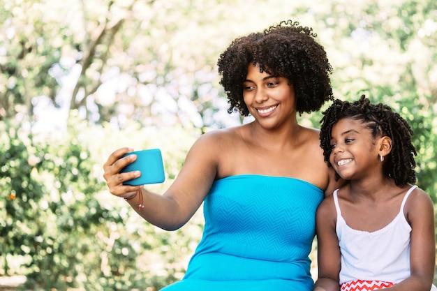 Portret van een afro-amerikaanse vrouw met een klein meisje dat lacht en vrolijk een selfie maakt
