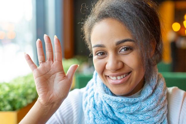 Portret van een afro-amerikaanse vrouw met een videogesprek. ze zwaait met haar hand en zegt hallo. close-up foto.