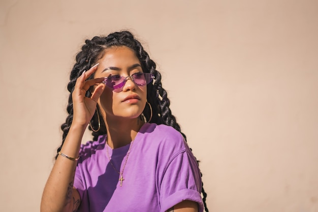 Portret van een afro-amerikaanse vrouw met lang haar, gekleed in een paars shirt en zonnebril