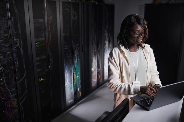 Portret van een afro-amerikaanse vrouwelijke netwerkingenieur die een laptop gebruikt terwijl hij in een donkere serverruimte werkt, kopieer ruimte