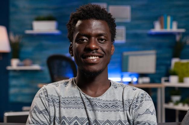 Portret van een afro-amerikaanse werknemer die in de camera kijkt terwijl hij op de bank rust