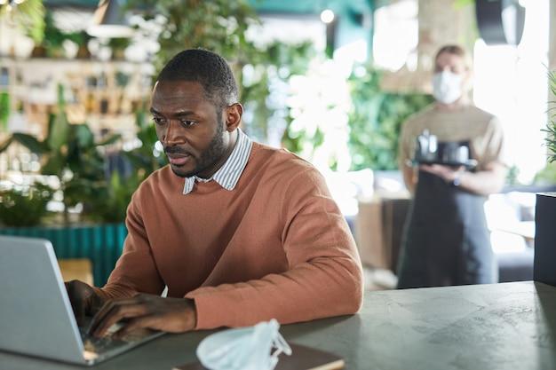 Portret van een afro-amerikaanse zakenman die een laptop gebruikt terwijl hij in een milieuvriendelijk café-interieur werkt, versierd met verse groene planten, kopieer ruimte