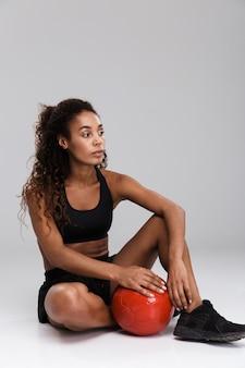 Portret van een afro-amerikaanse zelfverzekerde jonge fitte sportvrouw die oefeningen doet met zware bal geïsoleerd over grijze achtergrond, zittend, wegkijken