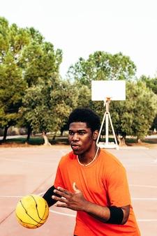 Portret van een afro-amerikaanse zwarte jongen die basketbal speelt op een stedelijk hof.