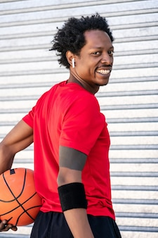 Portret van een afro-atleetmens die een basketbalbal houdt terwijl hij buiten staat. sport en een gezonde levensstijl.