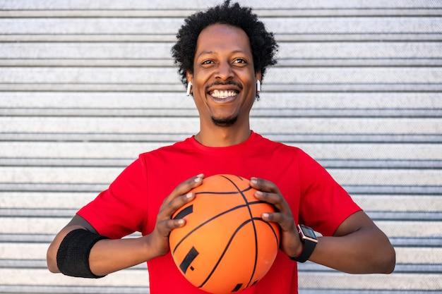 Portret van een afro-atleetmens die een basketbalbal houdt terwijl hij buiten staat