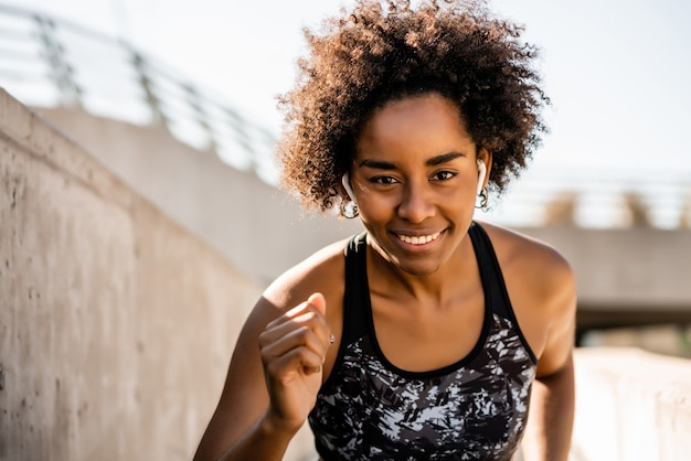 Portret van een afro-atleetvrouw die buiten loopt en oefeningen doet. sporten en een gezonde levensstijl.