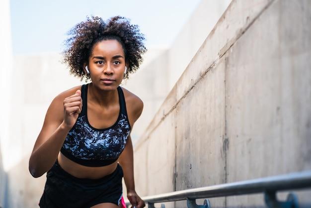 Portret van een afro-atleetvrouw die buiten rent en oefeningen doet