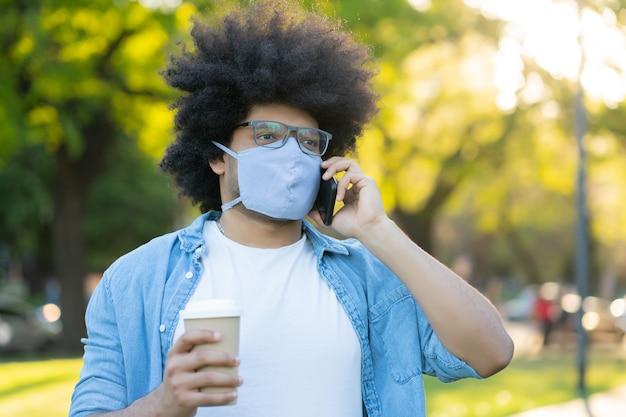 Portret van een afro latijns-man met gezichtsmasker en praten aan de telefoon terwijl hij buiten op straat staat