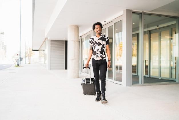 Portret van een afro-toerist die een koffer draagt terwijl hij buiten op straat loopt