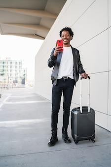 Portret van een afro-toerist die zijn mobiele telefoon gebruikt en een koffer draagt terwijl hij buiten op straat loopt. toerisme concept. Premium Foto