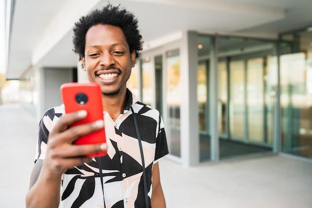 Portret van een afro-toeristische man met zijn mobiele telefoon tijdens het wandelen buiten op straat. toerisme concept.