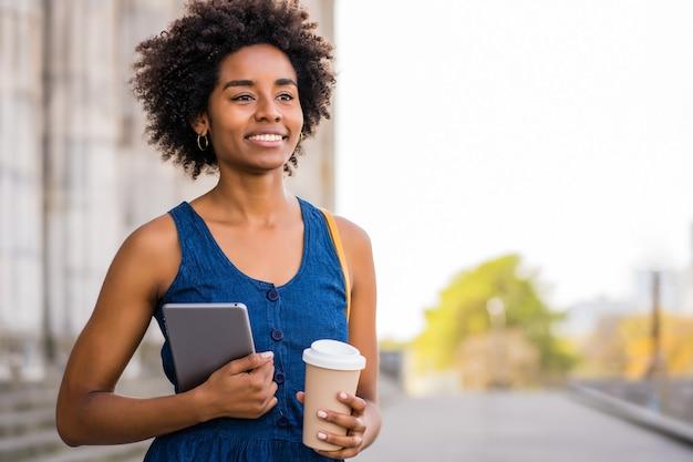 Portret van een afro zakenvrouw die een digitale tablet en een kopje koffie houdt terwijl ze buiten op straat staat. bedrijfs- en stedelijk concept.