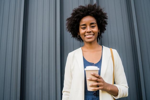 Portret van een afro-zakenvrouw die een kopje koffie vasthoudt terwijl ze buiten op straat staat