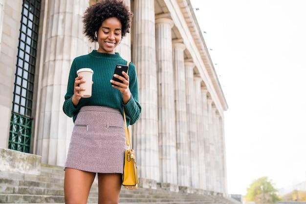Portret van een afro zakenvrouw met behulp van haar mobiele telefoon en een kopje koffie te houden tijdens het buiten wandelen op straat