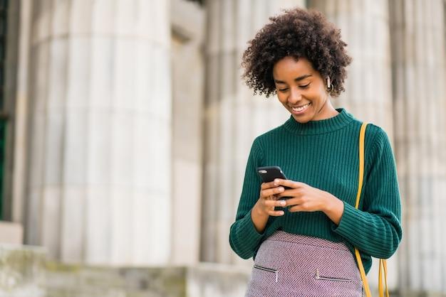 Portret van een afro zakenvrouw met behulp van haar mobiele telefoon terwijl ze buiten op straat staat