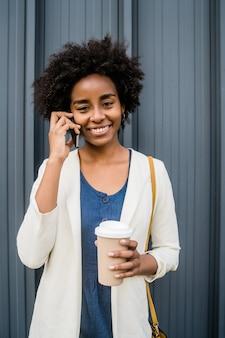 Portret van een afro zakenvrouw praten aan de telefoon en een kopje koffie vasthouden terwijl ze buiten op straat staat