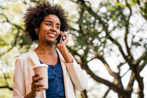 Portret van een afro zakenvrouw praten aan de telefoon en houdt een kopje koffie terwijl je buiten in het park staat. bedrijfsconcept.
