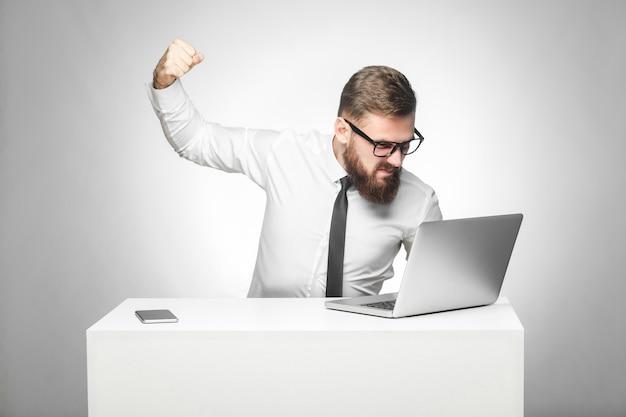 Portret van een agressieve ongelukkige zakenman die op kantoor zit en een slecht humeur heeft, staat klaar om een werknemer met een vuist en een boos gezicht door een webcam te slaan. indoor studio-opname, geïsoleerd op een grijze achtergrond Premium Foto