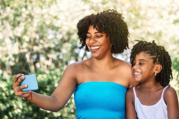 Portret van een alleenstaande moeder met haar dochter die naar haar telefoon kijkt of een videogesprek voert